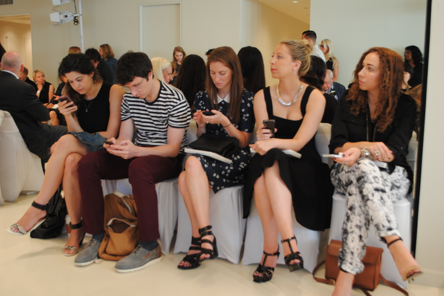 Hip looking fashionistas on their iphones using instagram. Duh.