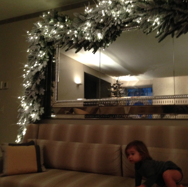 Baby Tusia sitting on the couch surrounded by white lights at the Winter Wonderland Natori apartment.