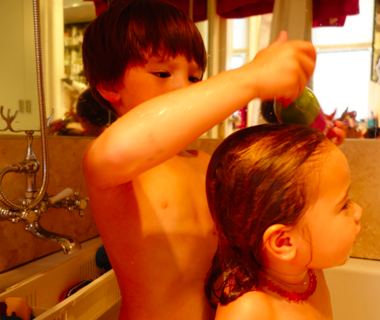 Big brother, Cruzzie, likes to spray the conditioner into Zoe's hair.