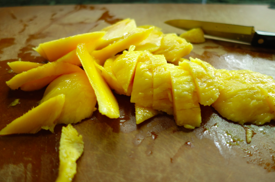 Cut the mango. And don't suck on the meat from the pit -- many women are severely allergic to a mango pit and don't know they are....until they look like a clown.