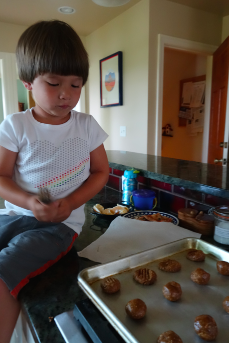 "Have a sous chef flatten the cookies out with fork imprints (making an ""X"")"