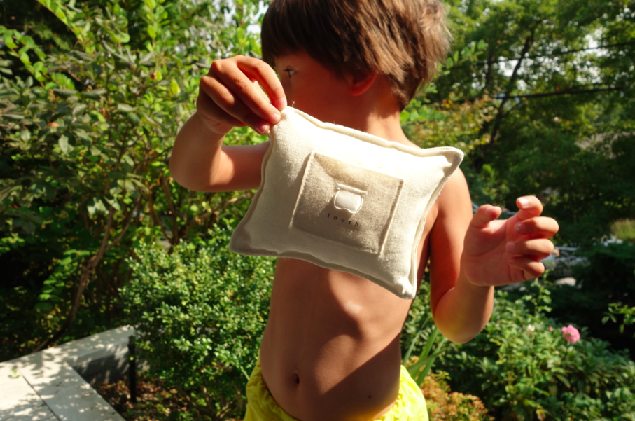 Nothing cries chic like a boy in a swimsuit holding a tooth pillow.