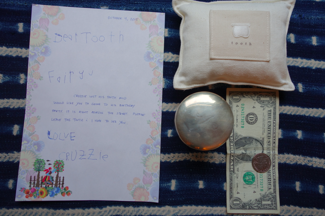 The goods for the teeth: the letter, the reward from the Tooth Fairy, the pillow, and a jar to keep the teeth (I know, gross, BARF, and yet still doing it).