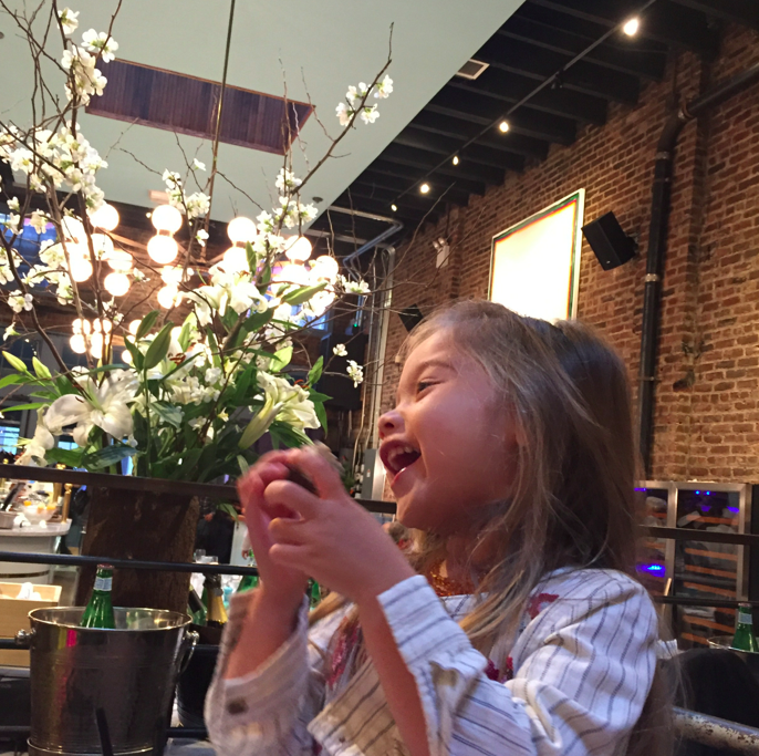 Laughing girl, brick walls, beautiful flowers, and tall ceilings.